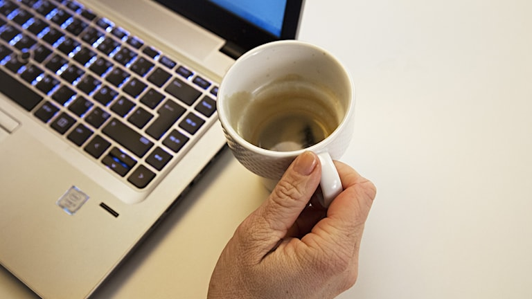 En hand håller i en kaffekopp framför en bärbar dator.