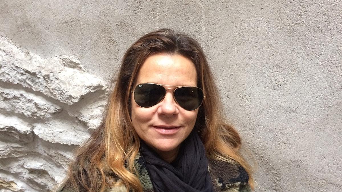 Katarina står framför en stenvägg, iklädd mörlka solglasögon