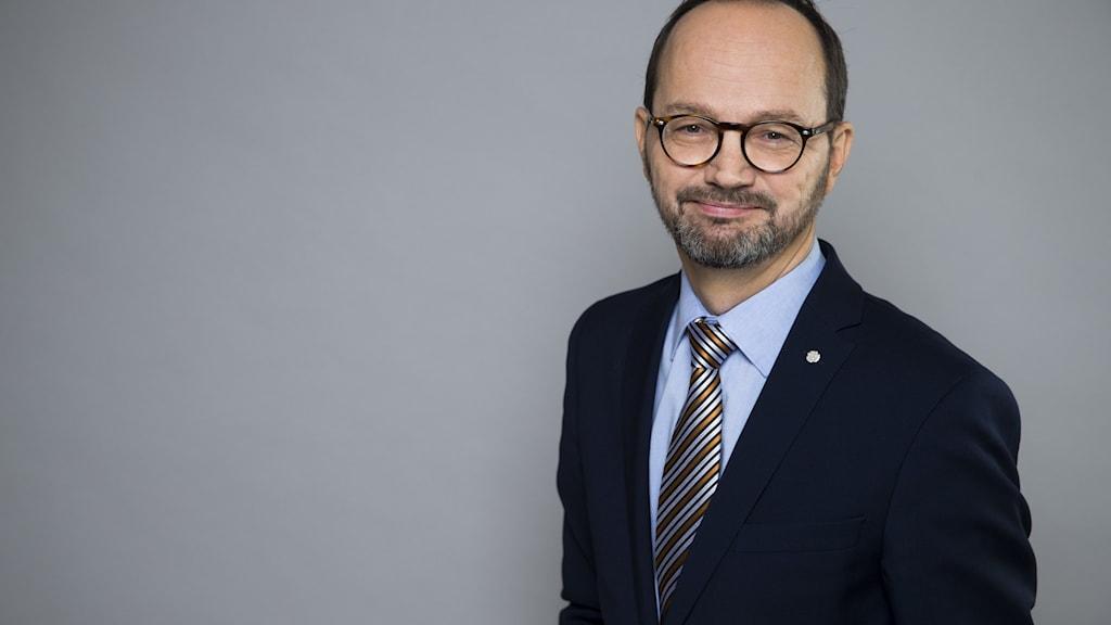 En man i glasögon, blå skjorta, slips och kavaj.
