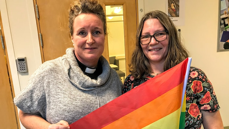 Pressvisning från Pride. Präst och representant från Pride står med en Prideflagga.