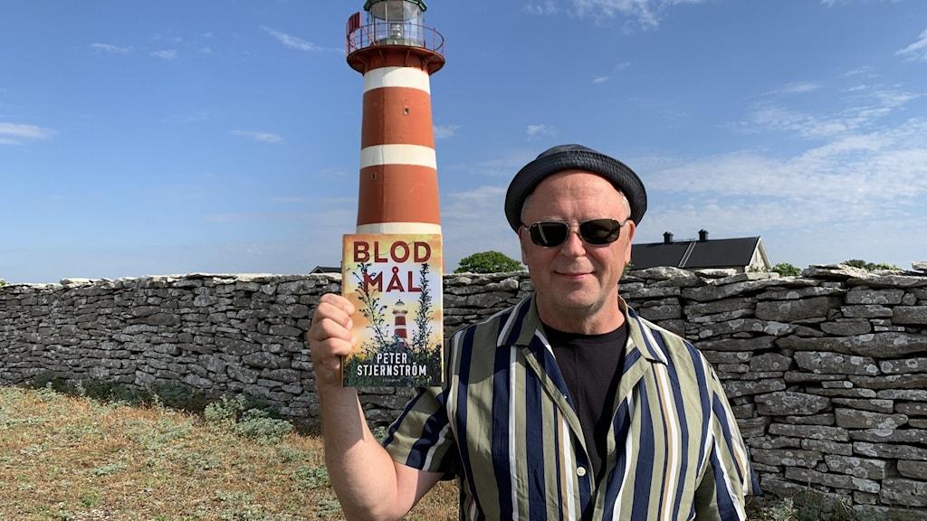 En man håller i en bok framför en rödvit fyr.