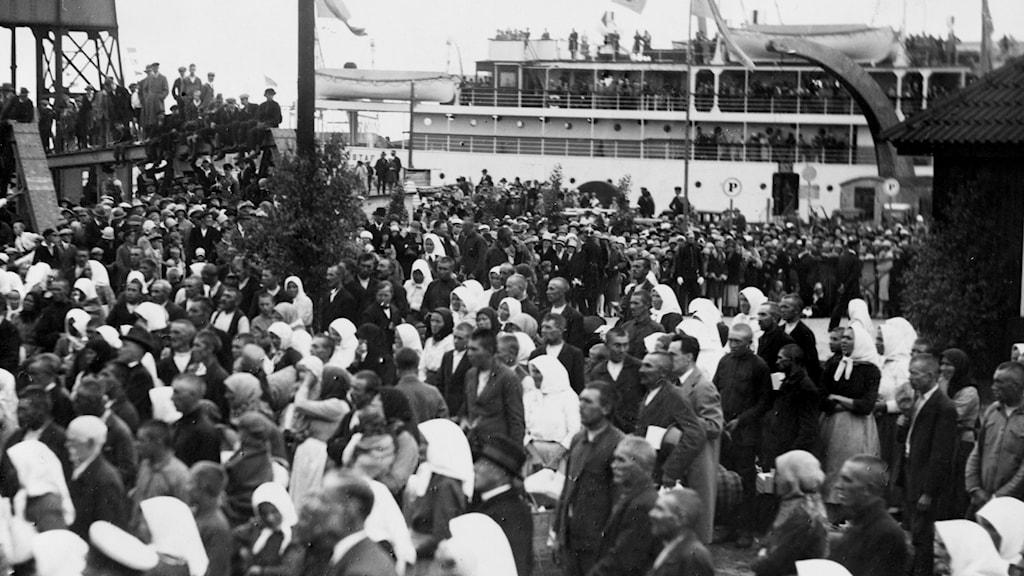1929: Gammelsvenskbybor just komna från Ukraina lyssnar till prins Carls hälsningstal i Trelleborgs hamn.