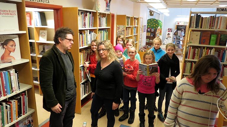 Läraren John Stövring och föräldern Lisa Blochmann med fårösundselever i biblioteket. Foto: Anna Jutehammar / SR Gotland