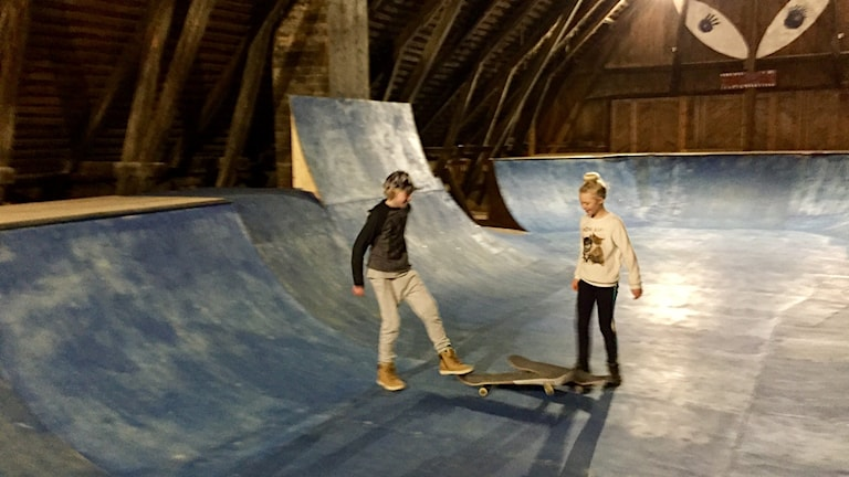 I familjens lada har en skateboardpark vuxit fram. Vi ser barnen Signe och Axel.