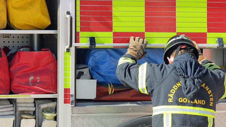 Brandman kontollerar utrusting på brandbil. Foto: Filip Joelsson/SR Gotland
