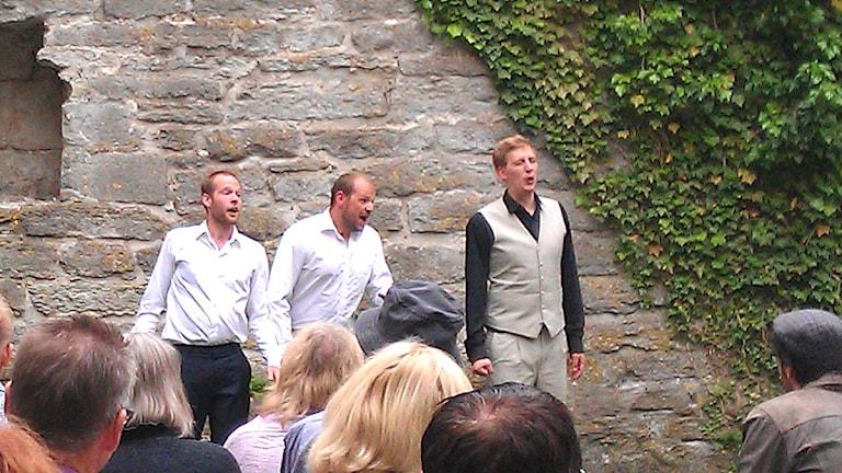 Henning von Schulman (t.h.) sjunger opera i S:t Clemens ruin tillsammans med några studiekamrater. Foto: Henrik Wallenius/P4 Gotland