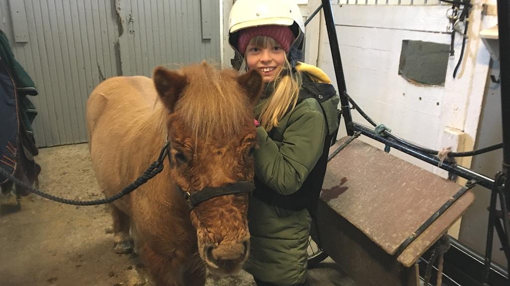 En tjej står bredvid en häst.