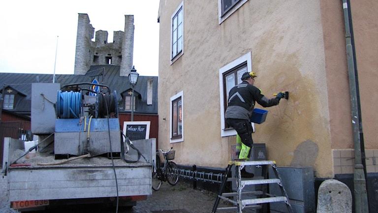 Per Thomsson sanerar klotter från en husvägg: Foto: Lasse Ahnell/P4 Gotland Sverigesradio