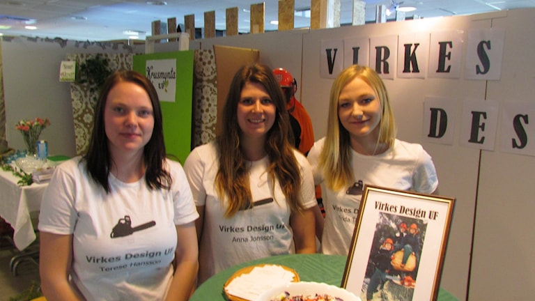 Tre unga tjejer står vid sin monter på mässan, iklädda vita tröjor med företagsloggan tryckt på bröstet.
