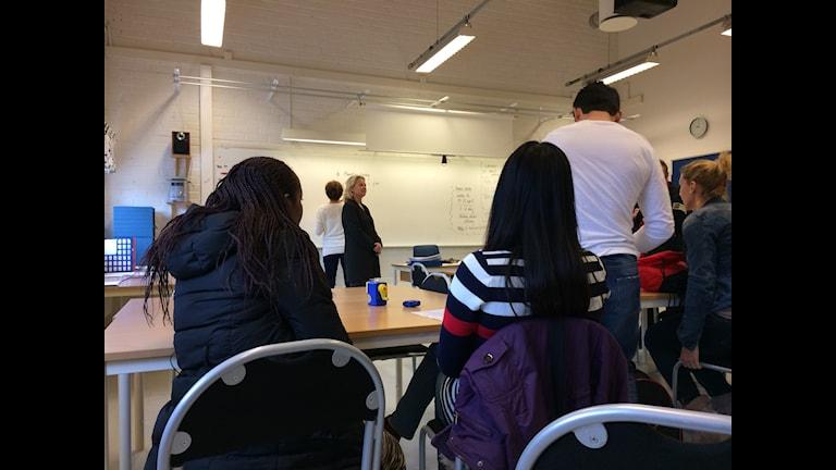 På bilden syns elever på SFI-utbildningen (Svenska för invandrare) som lyssnar till läraren framför dem.