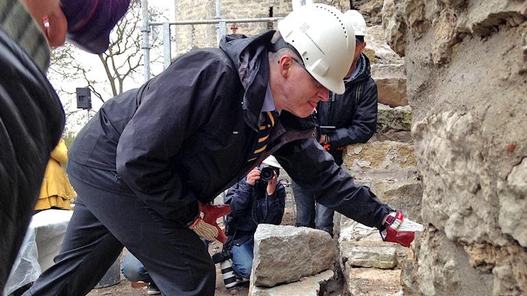 Här murar riksantikvarie Lars Amréus den första stenen vid murraset i Östergravar.