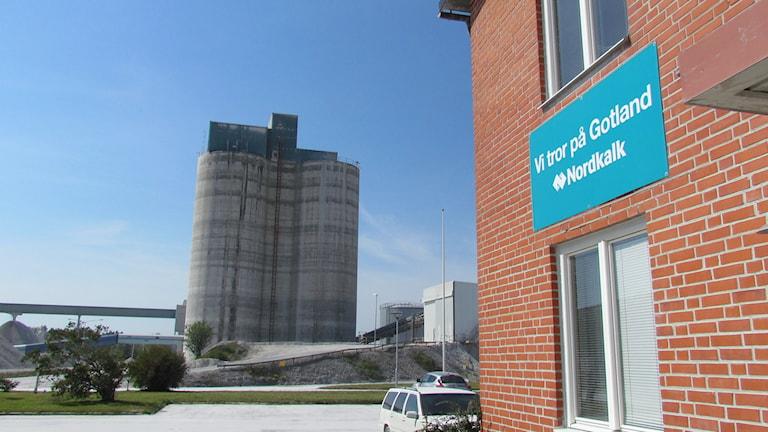 """En stor betongsilo i bakgrunden, i förgrunden Nordkalks tegelbyggda kontorsbyggnad med en stor blå skylt pa fasaden som säger: """"Vi tror på Gotland. Nordkalk"""""""