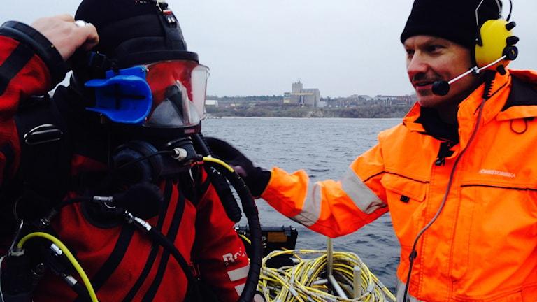 Jim Hansson får hjälp av Mikael Fredholm att hoppa i vattnet.