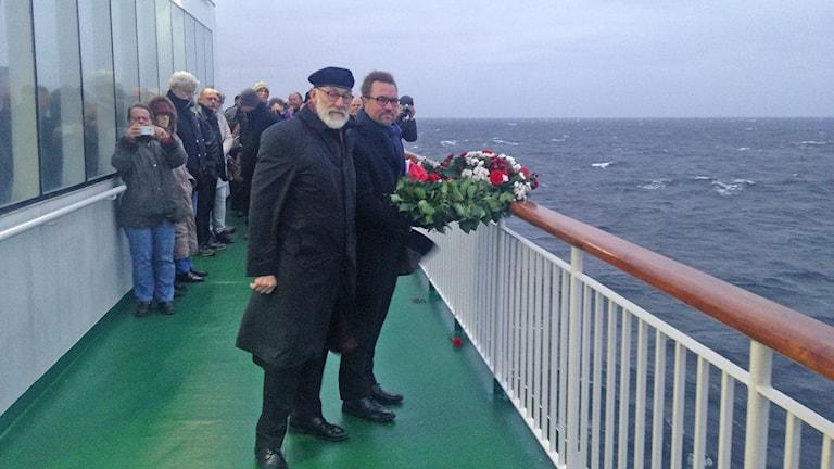 Prosten Lennart Kinnander och Håkan Johansson på Gotlandsbolaget lägger en krans vid platsen för Hansas förlisning. Foto: Anna Jutehammar/Sveriges Radio