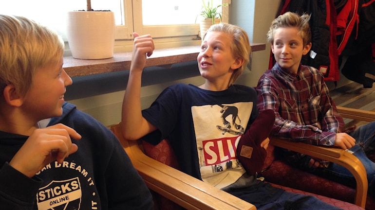 Tre pojkar sitter nedanför ett fönster som en av dem pekar på med tummen.