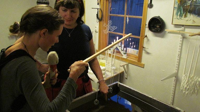 Amanda Heijbel lär sig stöpa ljus av Elisabeth Wickström. Foto: Patrik Olsson/Sveriges Radio