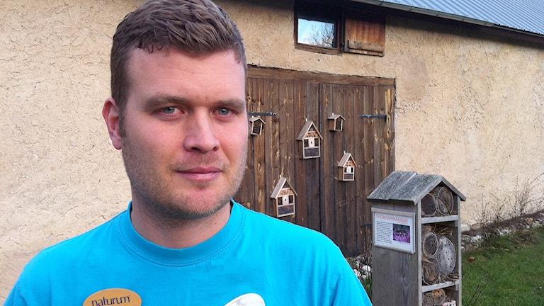 David Lundgren på Naturum i Vamlingbo och målansvarig på länsstyrelsen framför några biholkar, som bidrar till öka mängden bin. Foto: Daniel Värjö/Sveriges Radio