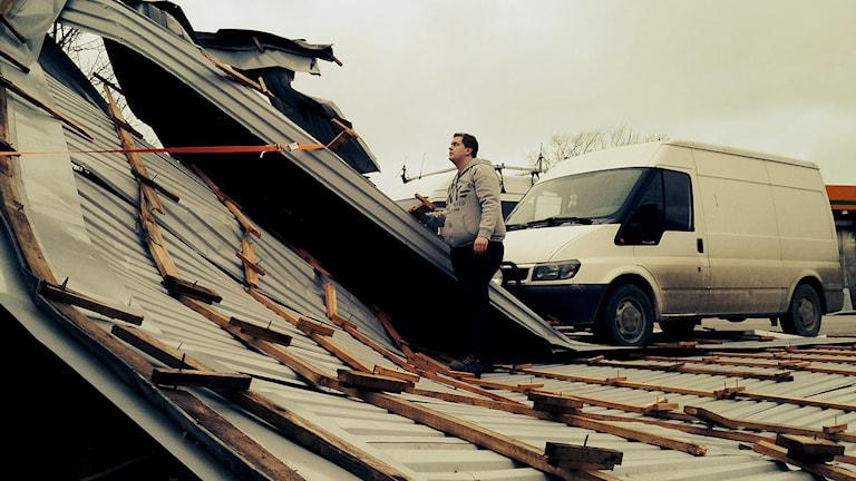 Joakim Jacobsson undersöker det avblåsta taket i Klintehamn. Foto: Olle Wiberg/Sveriges Radio
