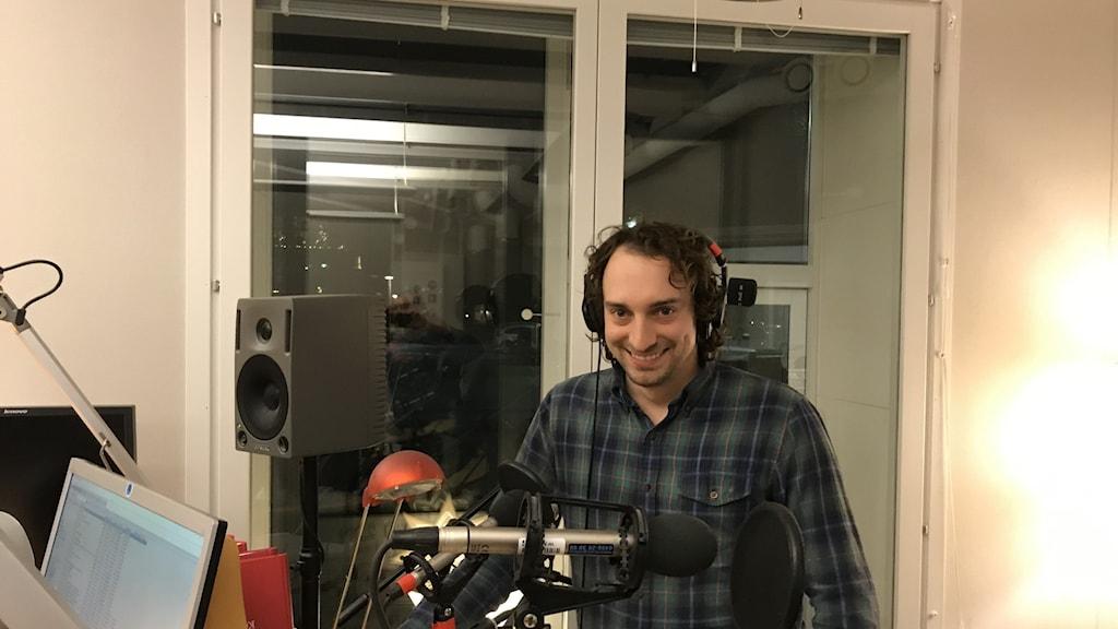 Michael står leende i P4 Gotlands radiostudio bakom en mikrofon.