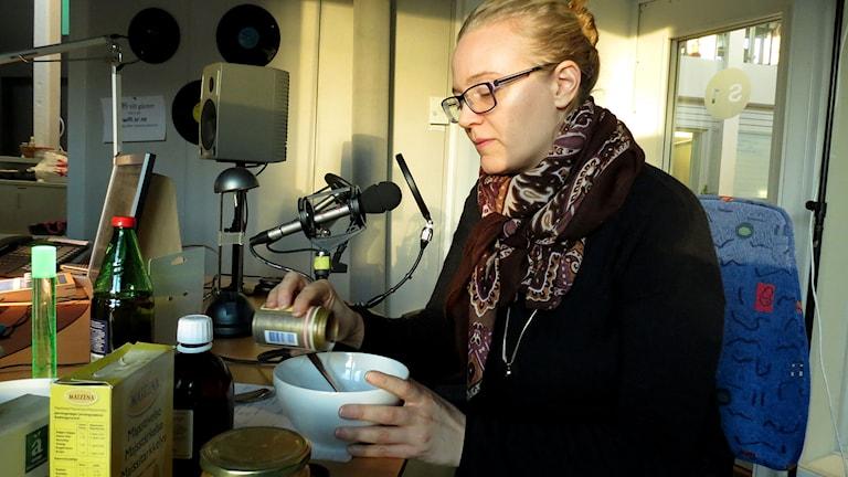 Annacarin Skarstedt blandar till en ansiktsmask av ricinolja och bikarbonat. Foto: Malin Nordström/Sveriges Radio.