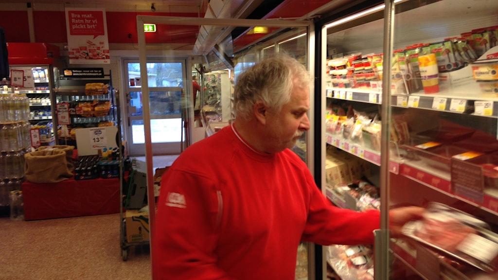 Mats Runander lägger in varor i kyldisken i sin butik.