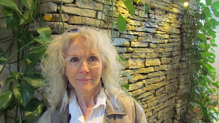 I stort blont lockigt hår tittar Merit Hemmingsson in i kameran genom guldfärgade tunna metallbågade glasögon.