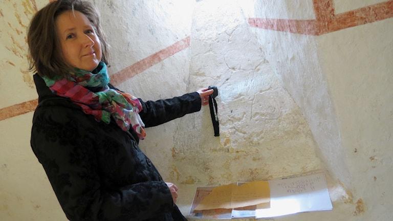 Arkeologen Laila Kitzler Åhfeldt med runinskriften i Hejnum kyrka. Foto: Håkan Erlandsson/Sveriges Radio