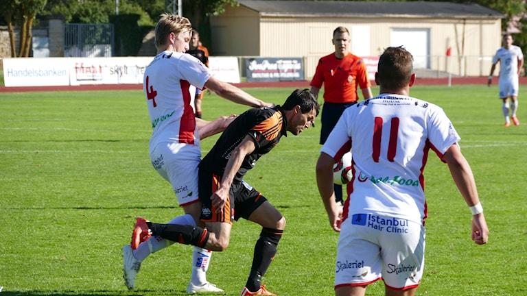 Goran Cuckovic i FC Gute i kamp med försvarare i Assyriska IF. Foto: Eva Didriksson/Sveriges Radio Gotland
