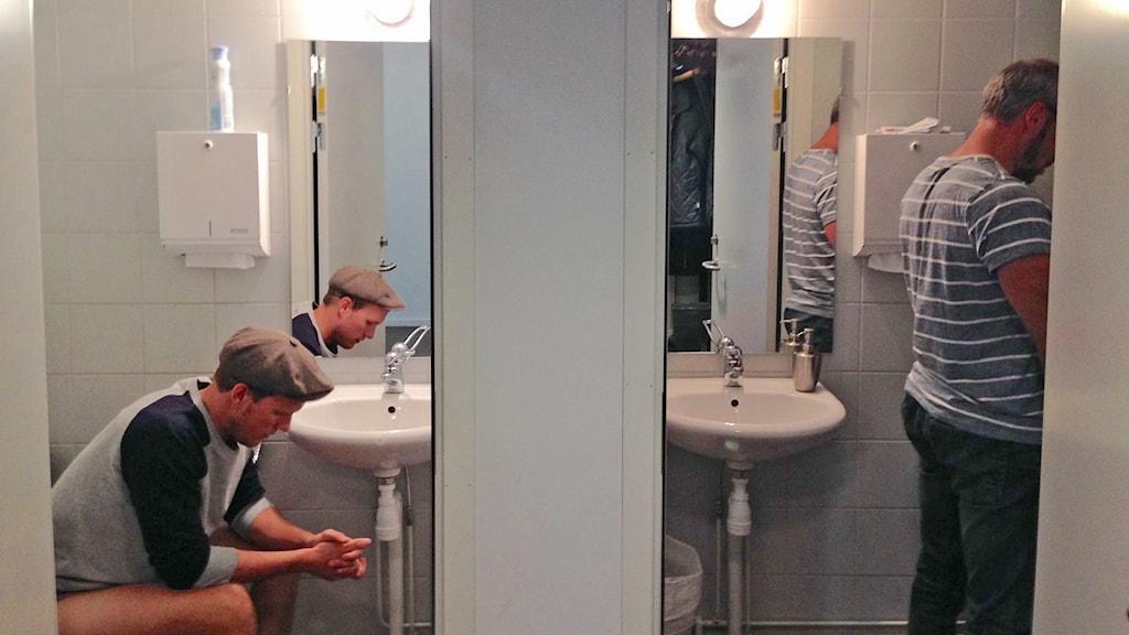 Män kissar - en sitter, en står. Foto: Sveriges Radio