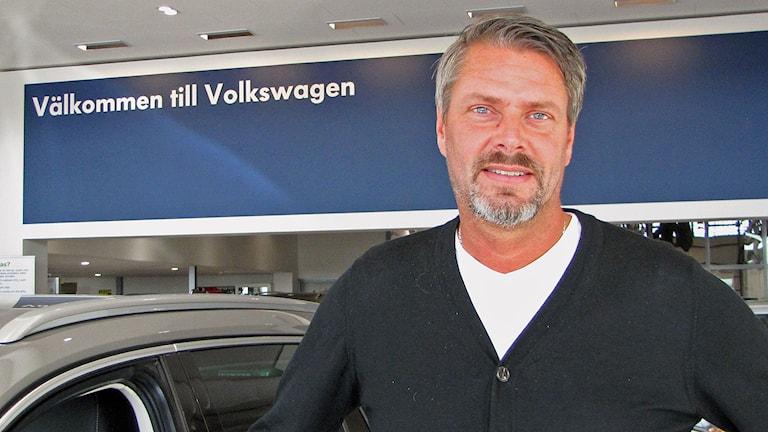 Roger Ogestad vd Bilcity Visby framför VWskylt Foto Lasse Ahnell Sverigesradio