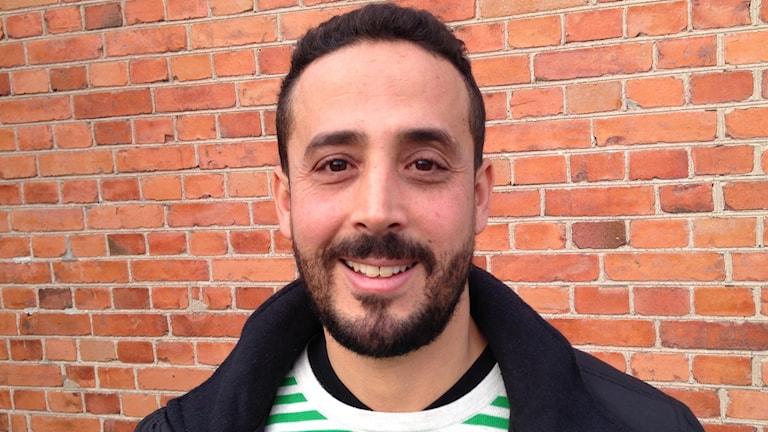Ahmed Arba står leende framför en tegelvägg