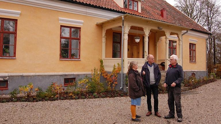 Pastor Anna Lena Olsson, kyrkoherde Benny Helgesson och kyrkorådets ordförande framför prästgården i Garda. Foto: Jack Lantz/Sveriges Radio