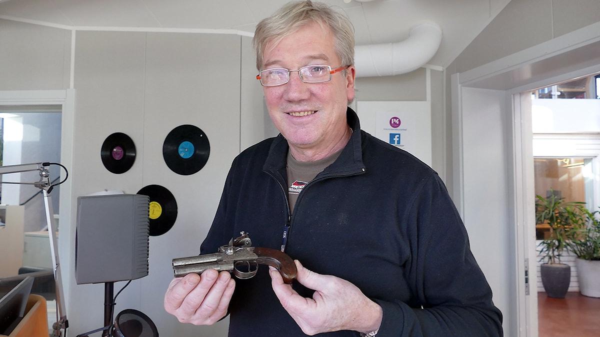 Antikexperten Ulf Broberg granskar en mynnigsladdare. Foto: Jonas Neuman/Sveriges Radio