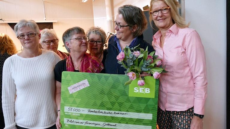 Bröstkollen lämnar över check till Bröstcancerföreningen. Foto: Jonas Neuman/Sveriges Radio