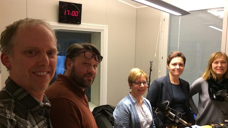 Fem personer står på rad i radiostudion, sköterskorna Magnus och Niclas närmast kameran, därefter cheferna Lena, Lotta och Yvonne.