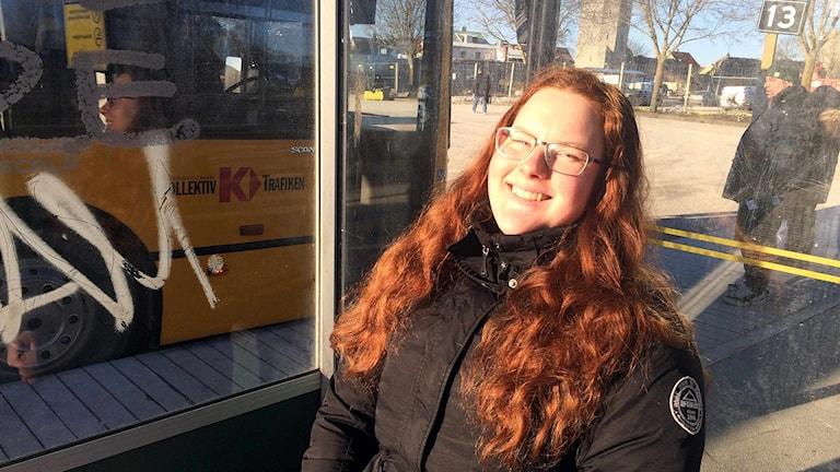 Rebecka Norrby solar vid busshållplatsen.