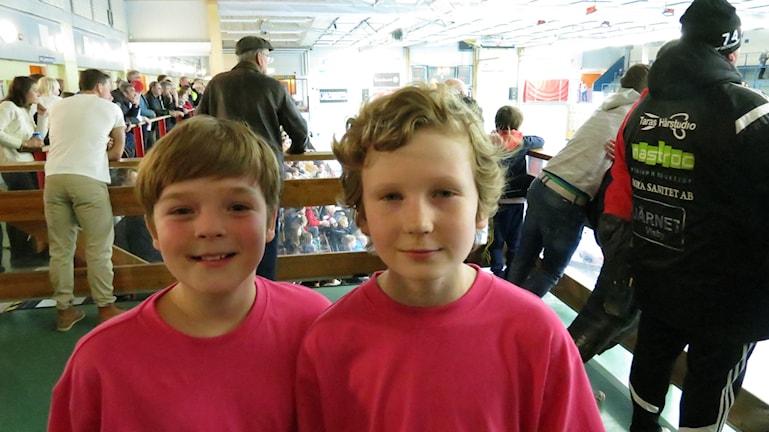 Leo Svahn och Filip Olofsson i rosa lagtröjor på läktaren med planen ibakgrunden.