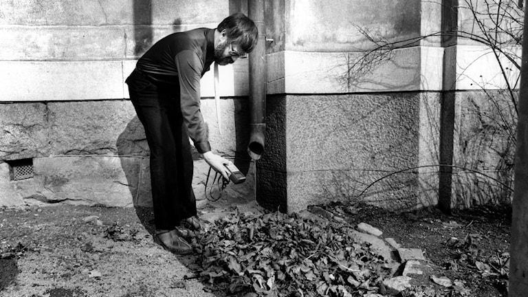 En man med en geigermätare kontrollerar de radioaktiva halterna av cesium i sin trädgård efter Tjernobylolyckan.