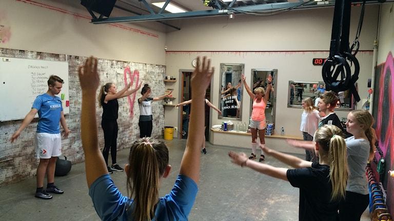 Ungdomar runt lokalen sträcker armarna uppåt, längst bort från kameran står passledaren och ger instruktioner.