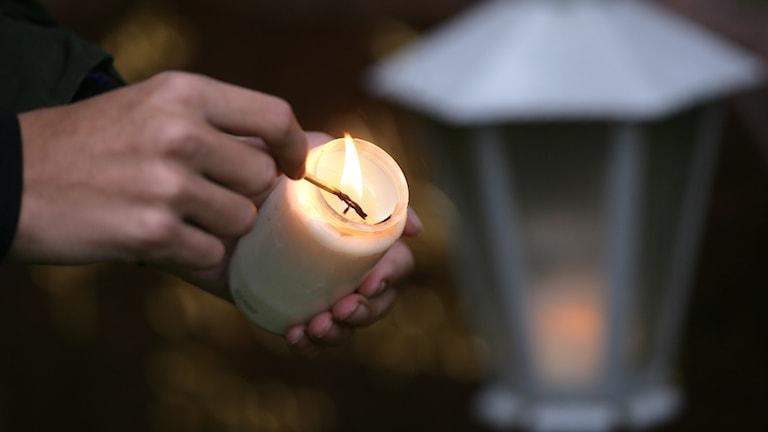Ett ljus tänds vid en grav under allhelgonahelgen.