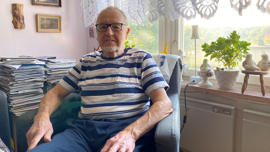 En äldre man i en fåtölj i hemmamiljö.