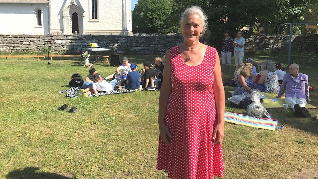 Gunilla Sundberg framför Garda kyrka på sin sista skolavslutning. Hon står i röd sommarklänning, medan eleverna fikar i bakgrunden.