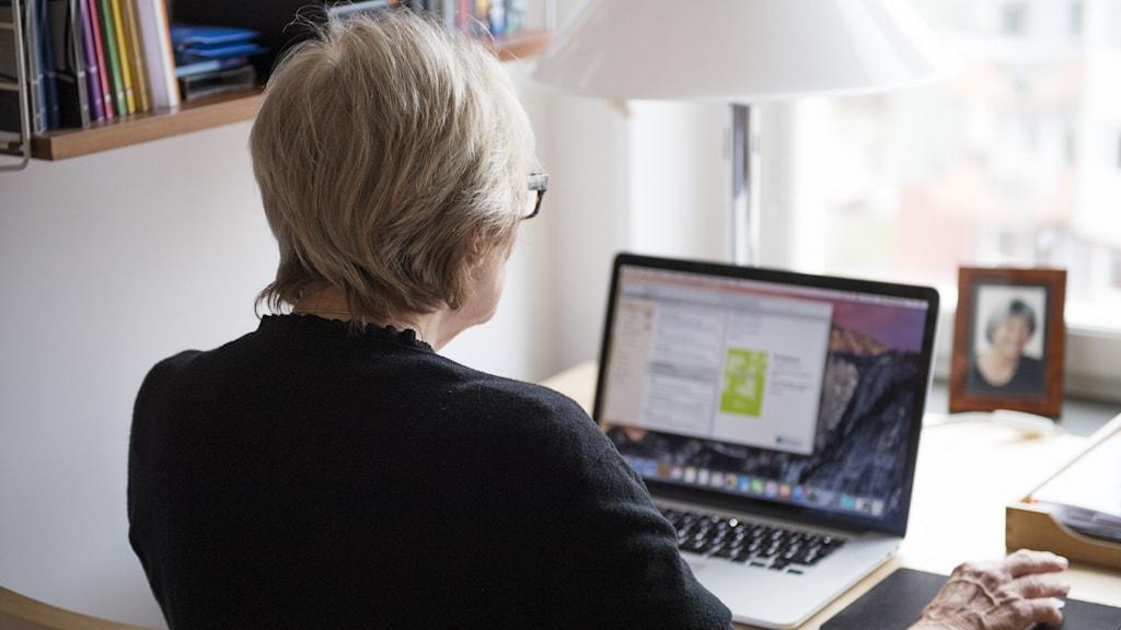 Pensionär sitter vid bärbar dator