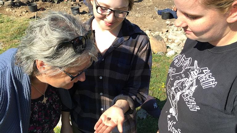 Arkeologerna Sabine Sten, Karin Mattsson och Sara Jonsson tittar på en glaspärla från järnåldern