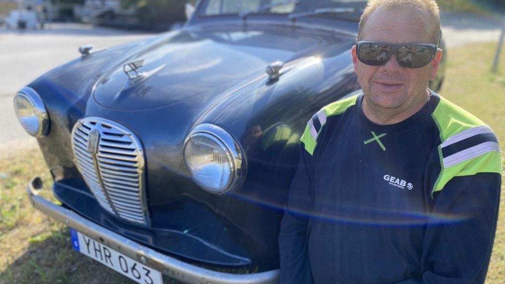 En man i solglasögon står bredvid en gammal bil.