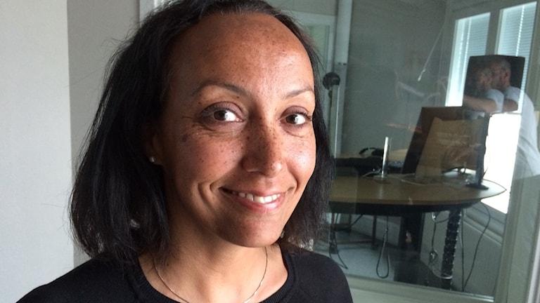 Elene Negussie ler mot kameran i radiostudion