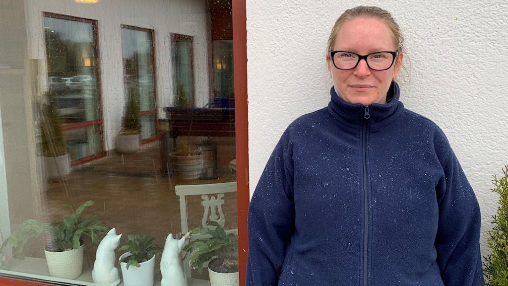 En kvinna i blå fleecejacka och svarta glasögon står utomhus framför en vit vägg och ett rött fönster.