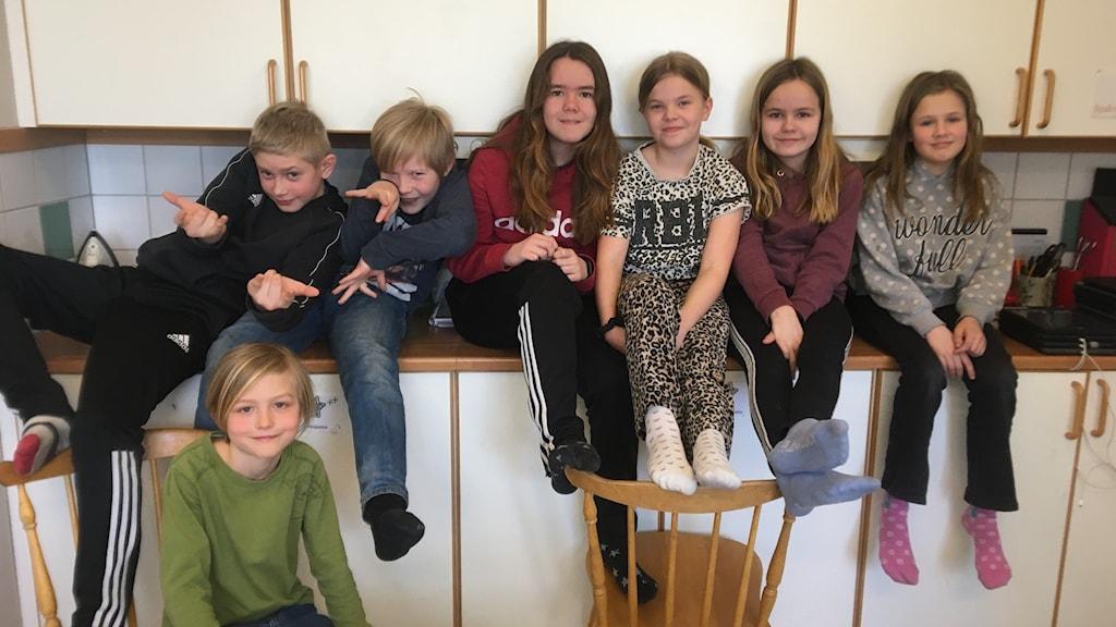 Sju barn sitter i ett kök på ett fritids.