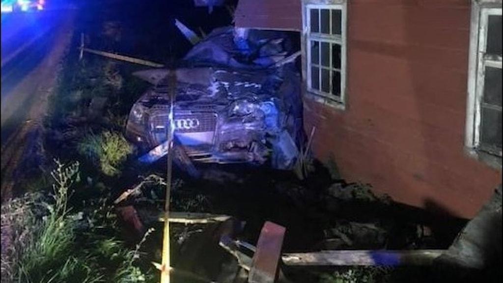 En bil är halvt inne i en ladugård efter en olycka.