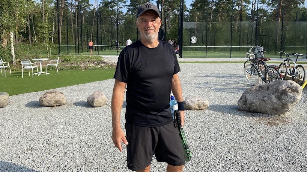 En man i svart tshirt, shorts och keps står framför en padelbana.